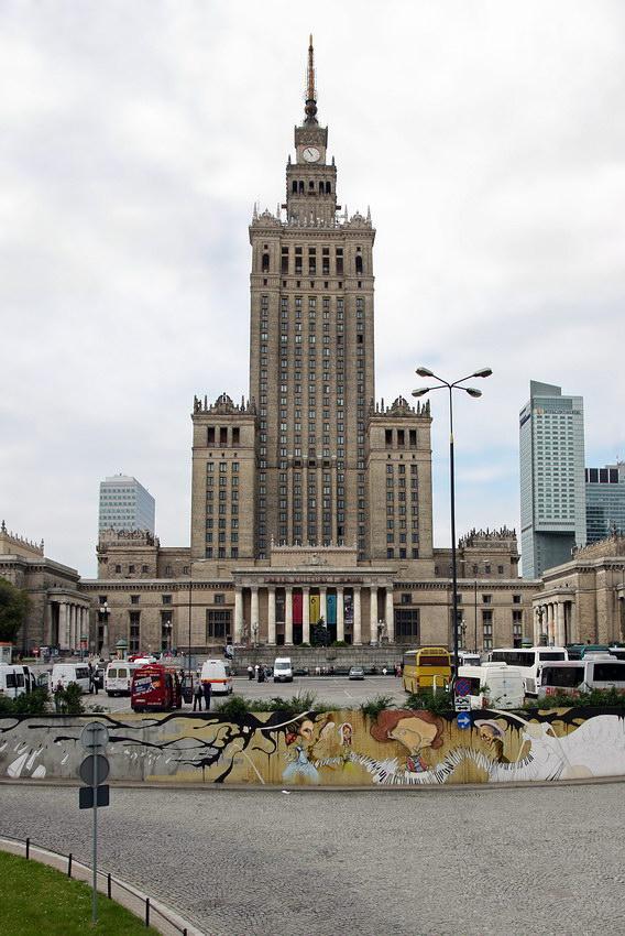 Foto do Palácio a preencher toda a parte de cima da foto. A meio o parque de estacionamento e em baixo a rua e um mural pintado numa parede