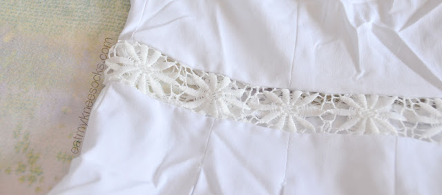 Close-up of the floral crochet/lace detailing along the waist of the white Fanewant romper.
