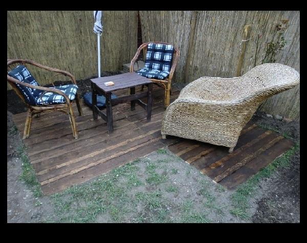 Peque o patio exterior revestido con for Como hacer un piso con palets