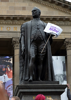 "Statue of Sir Redmond Barry, holding a sign, ""Equality Now"""