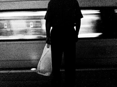 Man with shopping bag awaits train in Washington DC's subway system. Gallery Place/Chinatown Metro .