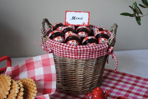 panier rempli de petit pots de confiture sur nappe vichy rouge