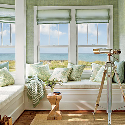 Window seat vignette with an ocean view in Coastal Living Magazine showhouse with wood floor, a seagrass area rug, a telescop, mint sea grass wallpaper, Mint roman curtains on casement windows, and a COCOCOZY Logo Throw