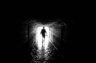 Light at the end of the tunnel, man standing in dark