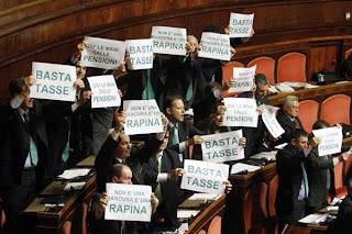Lega: Urla e cartelli in aula, intanto deputati padani si dimettono per garantirsi il vitalizio subito e non a 60 anni.