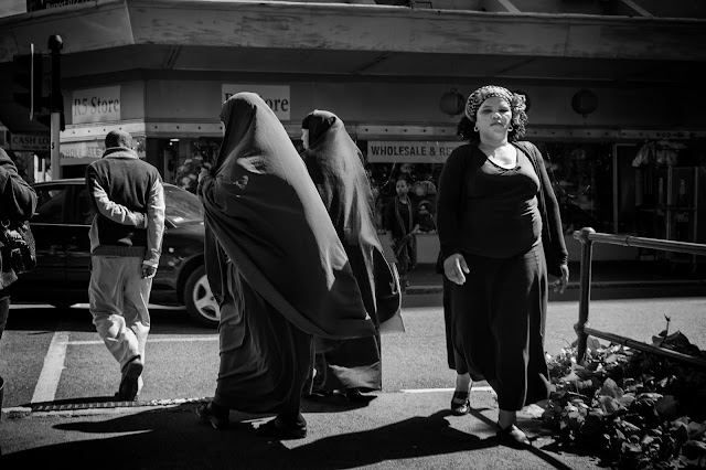 Two women in burkas follow a man as another woman walks past in this street photograph