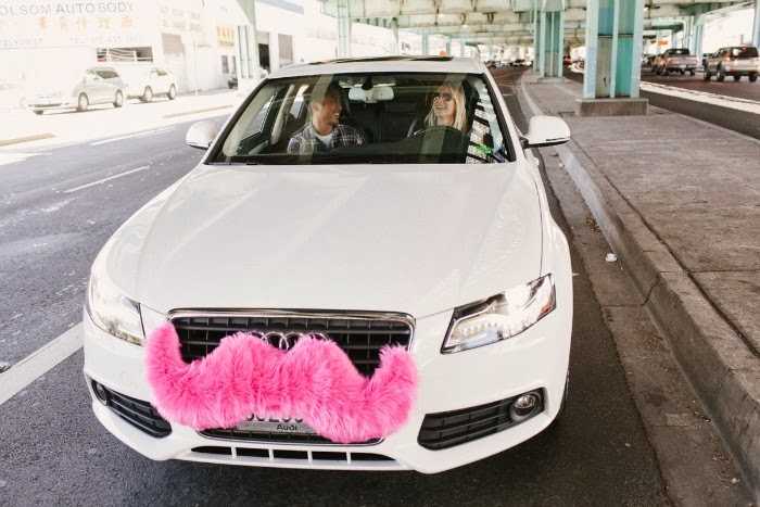 A white audi with a pink Lyft mustache on the front.