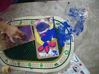 Szöveg: Ekkor állt égnek a hajam... Kép: Konyhai asztal letakarva vászonterítővel. Rajta egy tányéralátét, amin két szalaparkett darabon kék, piros, sárga, fehér festékfoltok vírítanak. A másik fadarabon már lila kevert festékből parafepecsétez egy gyermekkéz.