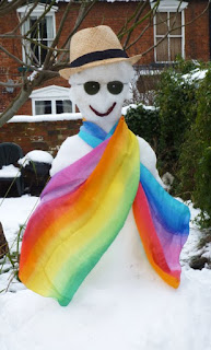 Snowman wearing sunglasses, strawhat & rainbow scarf