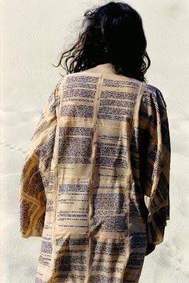 Mulher de costas, vestida com túnica feita de páginas de um livro