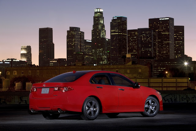 Rear three-quarters view of red 2012 Acura TSX on rooftop garage at dusk with downtown Los Angeles skyline