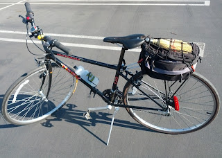 Whisk broom under cargo net atop bag mounted on rear bicycle rack.