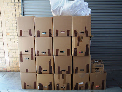 A pile of cartons stacked up next to a roller door in a warehouse.