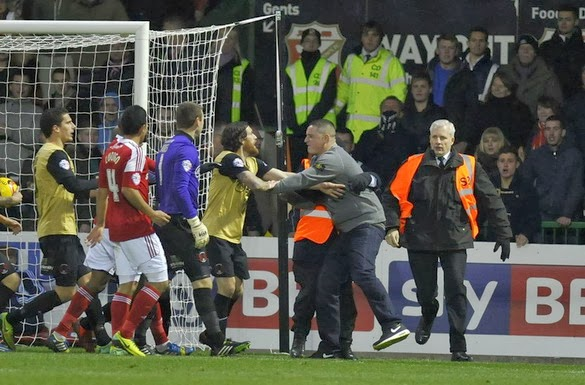 A pitch invader is being restrained after punching Leyton Orient goalkeeper Jamie Jones