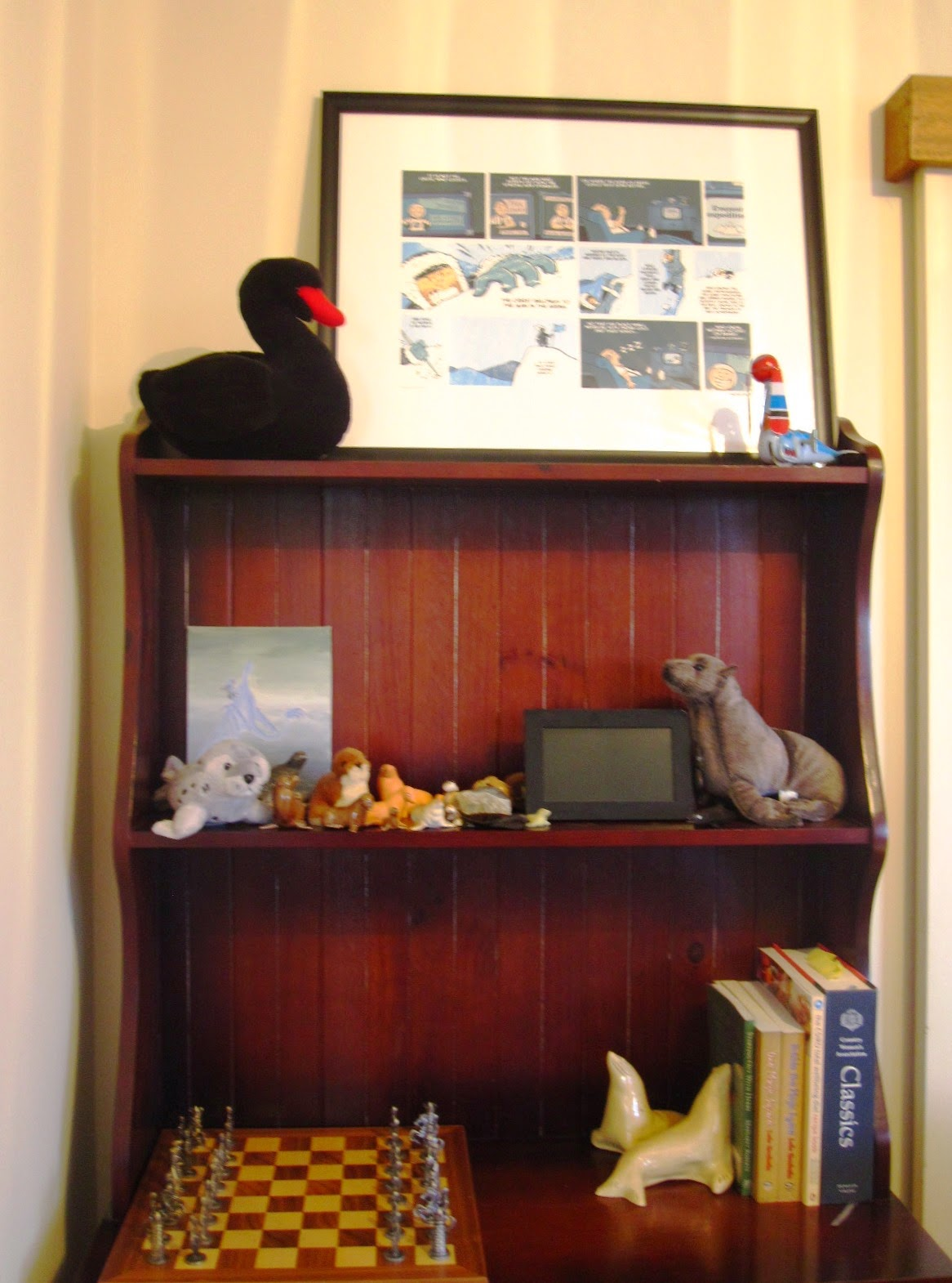 A small hutch dresser displaying a collection of seals of ciffernt materials (stuffed toys, stone, shell) and an ornate chess set.