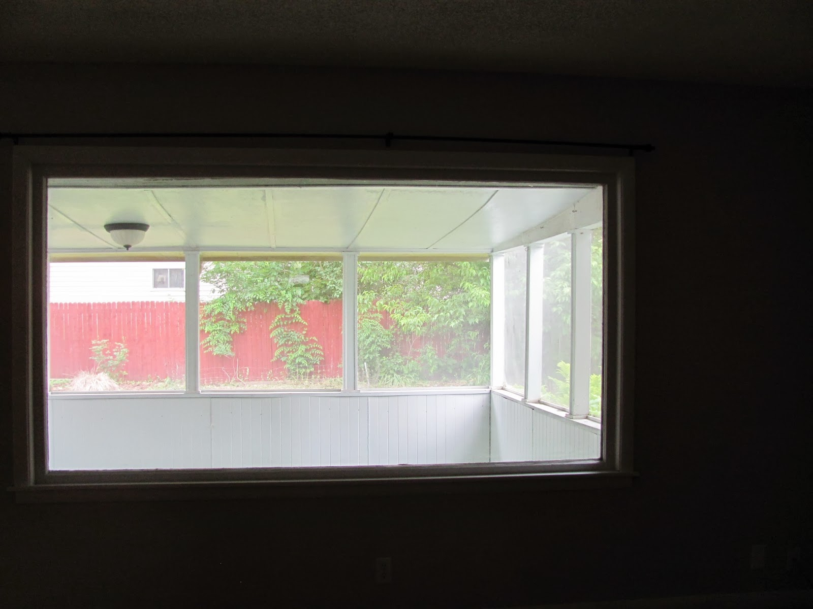 The screen porch is seen through the large window in the living room