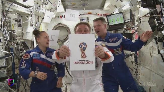 Científicos de la Estación Espacial Internacional mostrando el logo de Rusia 2018