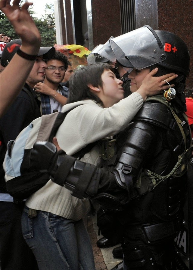 35 moments of violence that brought out incredible human compassion - a student protesting education reform leans in to kiss a riot officer