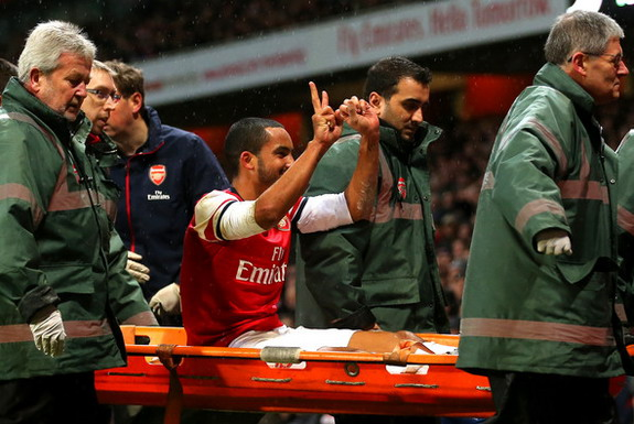 Arsenal player Theo Walcott makes a 2-0 gesture to the Tottenham fans as he is stretchered off