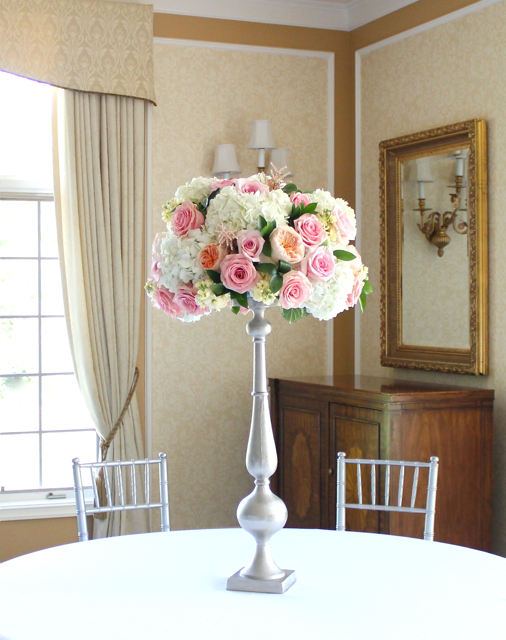 Tall silver pillar holder tall abundant guest table centerpiece for ann arbor wedding at barton hills country club peach garden rose juliet coral roses white hydrangea stock astilbe elegant abundant mound of soft lush blooms by sweet pea floral design ann arbor detroit