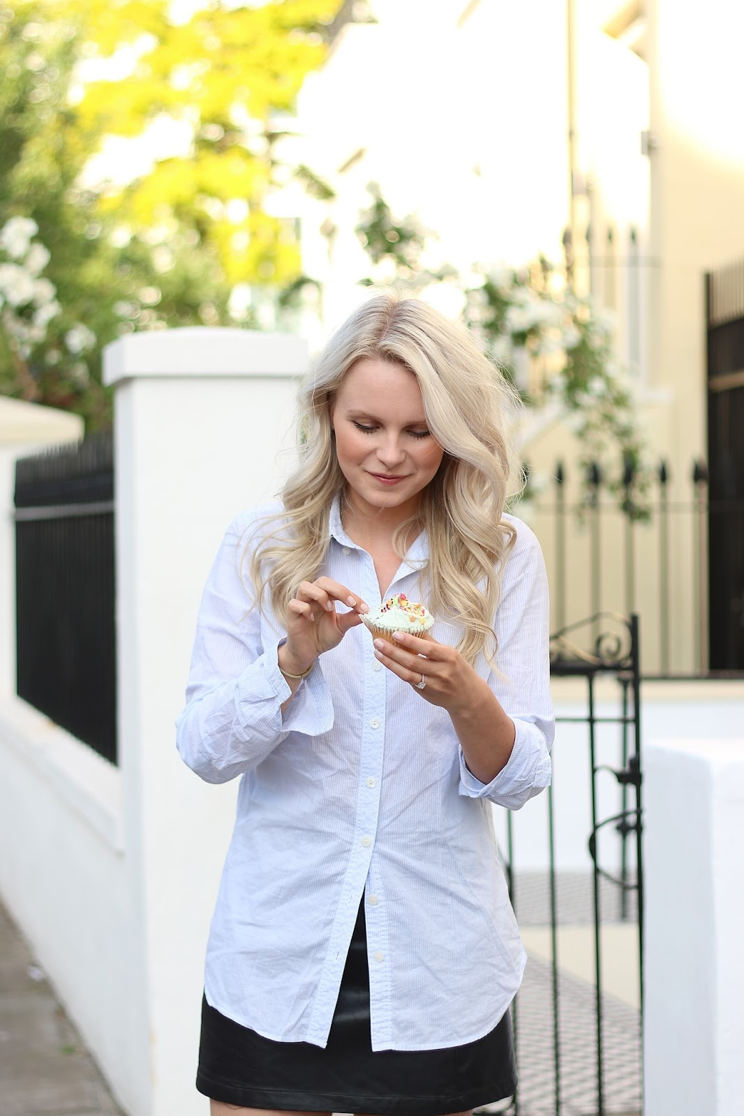 a girl wearing a blue button up shirt eats a vanilla cupcake on a sunny day in notting hill, london