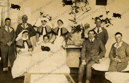 Photograph of patients and nursing staff, with one patient in bed, holding a black cat, in an unidentified hospital, 1914 - 1918 (D/DLI 7/63/6(17))