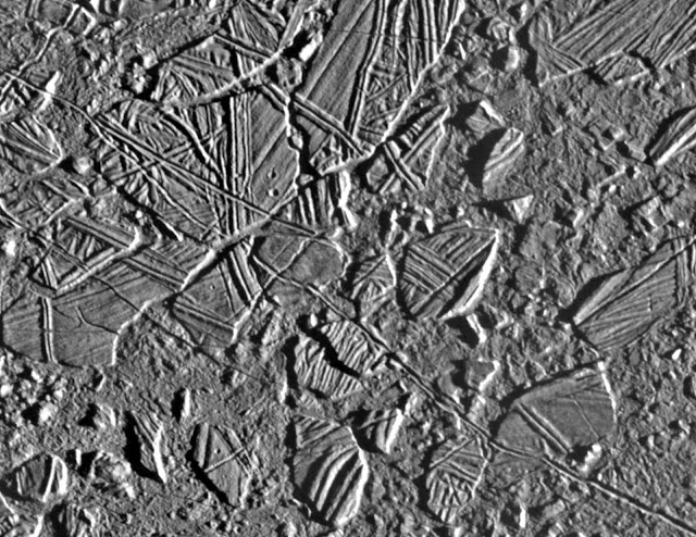"On Europa, ""chaos terrains"" are regions where the icy surface appears to have been broken apart , moved around, and frozen back together. Observations by Caltech graduate student Patrick Fischer and colleagues show that these regions have a composition distinct from the rest of the surface which seems to reflect the composition of the vast ocean under the crust of Europa. Credit: NASA/JPL-Caltech."