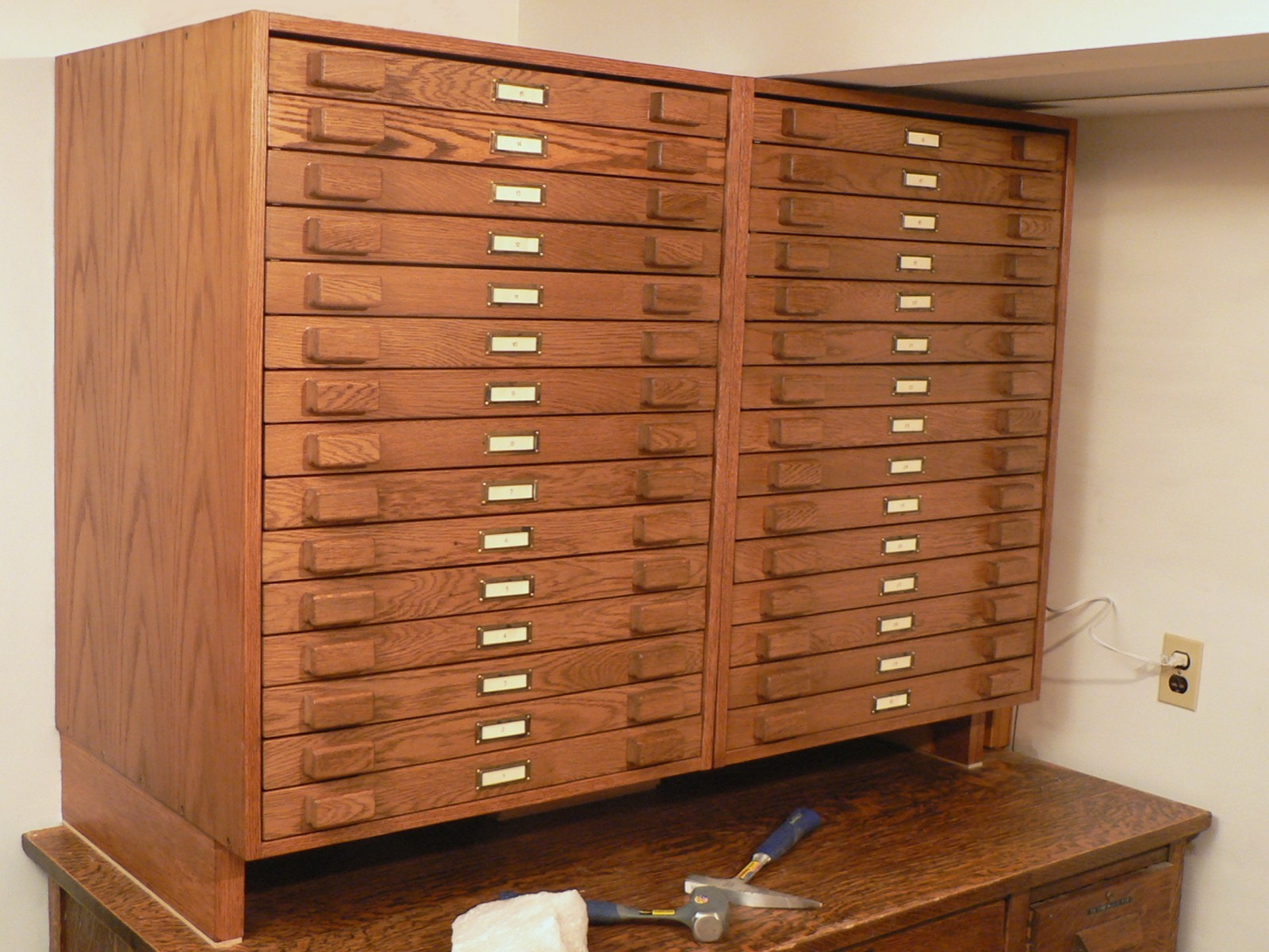 High Quality The Two Identical Cabinets, Each Housing 15 Drawers, Are Mounted On A  Pedestal On An Old Oak Desk.