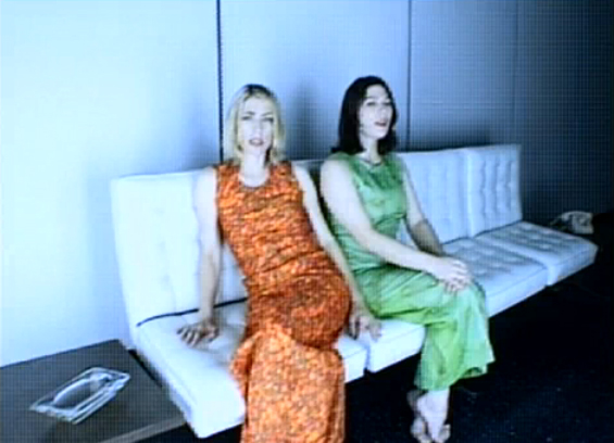 Sonic Youth's Kim Gordon in a beautiful 90's shiny orange dress with Kim Deal of The Pixies and The Breeders in a green dress. Still / screenshot from Little Trouble Girl (1995)