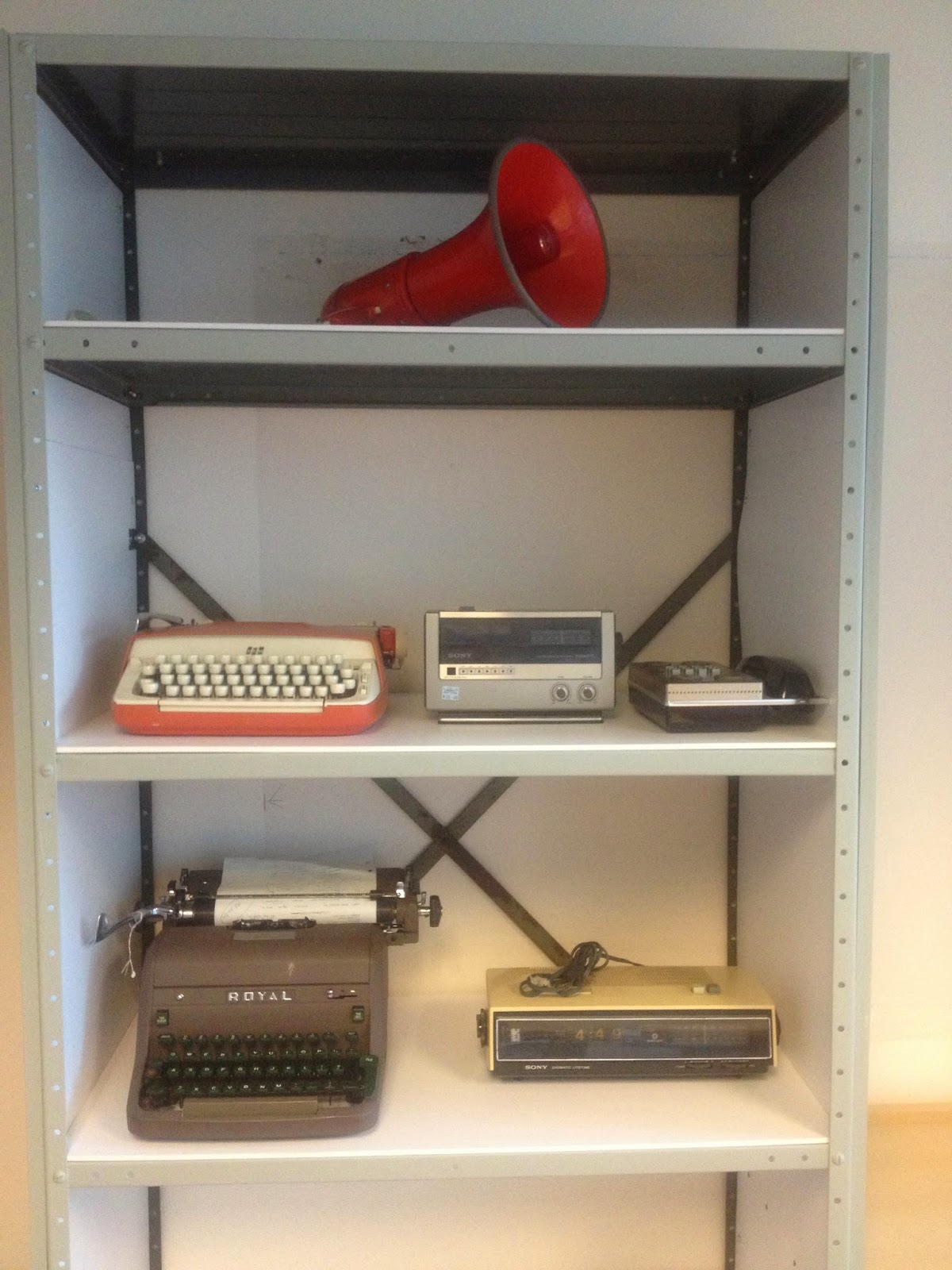 Collected artifacts on shelves from the late seventies. A red bullhorn, two typewriters, a radio, clock, and dial pad phone sit on the shelves.