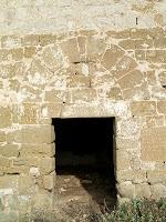 La façana de migdia de Sant Jaume d'Olzinelles amb la porta actual i l'arc adovellat de l'antic portal