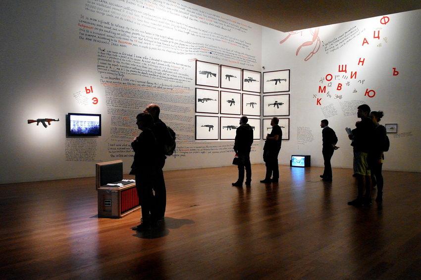 Uma sala com as paredes escritas e um conjunto de quadros com uma metralhadora cada um. Um televisor no chão, outro na parede e uma metralhadora na parede iluminada por um foco de luz. Várias pessoas pela sala a apreciarem os trabalhos