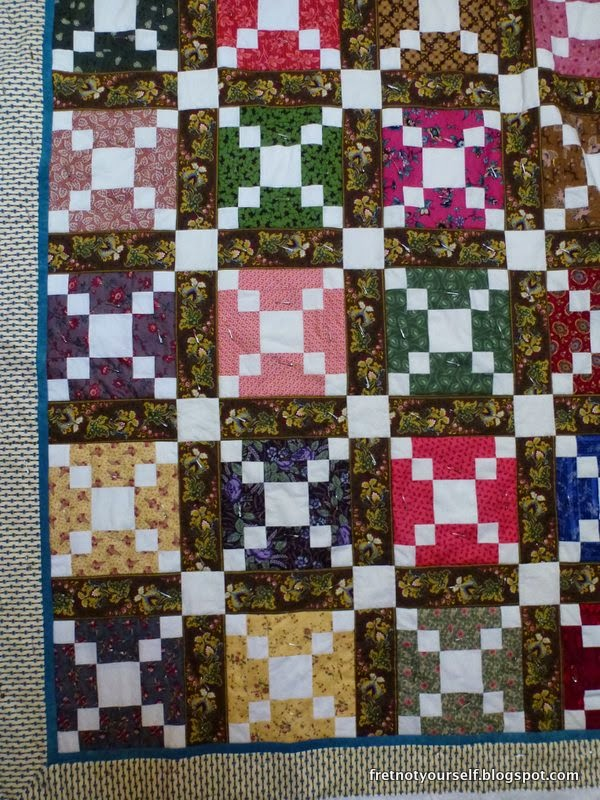 Reproduction fabrics in many colors alternate with muslin in this quilt.