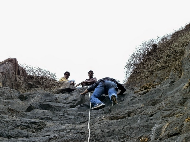 Shashank climbing the 40 feet rock patch on Madan with help from the local guides