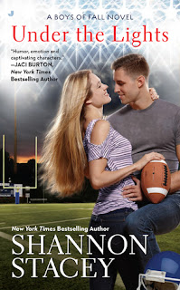 Cover description: a blond couple embrace on a football field. She's holding a football.