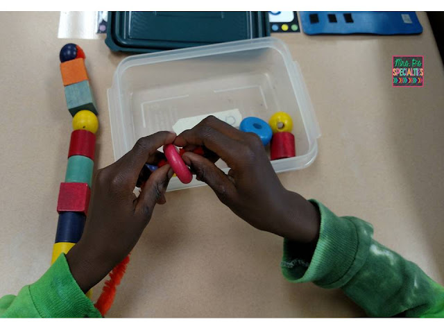 photo of student stringing beads onto a pipe cleaner