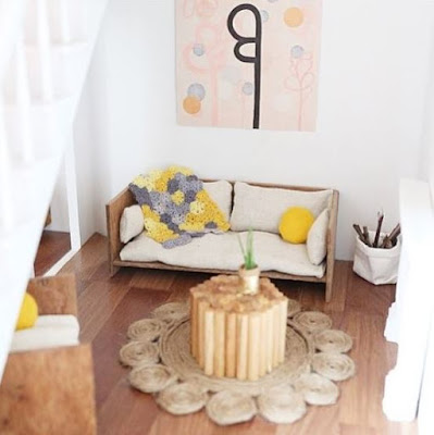 Modern dolls' house miniature lounge in pale shades, with grey and yellow accents, including a granny square rug.