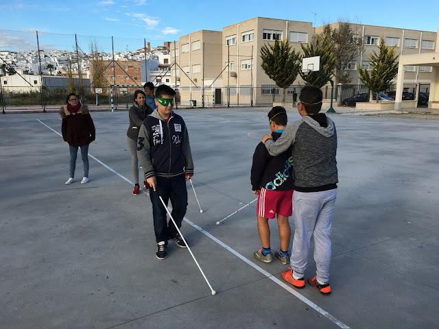 alumnos con antifaces y con ayuda del bastón y la guía de un compañero realizan un itinerario