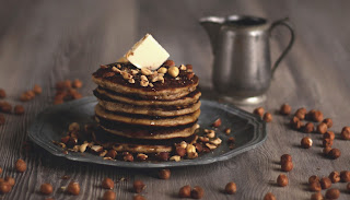 An elegant and classy stack of pancakes with hazelnuts, butter and maple syrup... An energy and brain booster recipe brought to you by the German foodblog Pancake Stories.