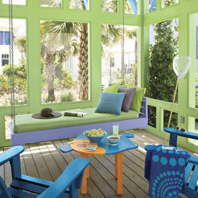 This bright and colorful coastal porch has vibrant greens and blues, perfect for a relaxing beach day