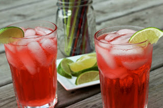 cherry limeade cocktail with a plate of lime wedges in the background
