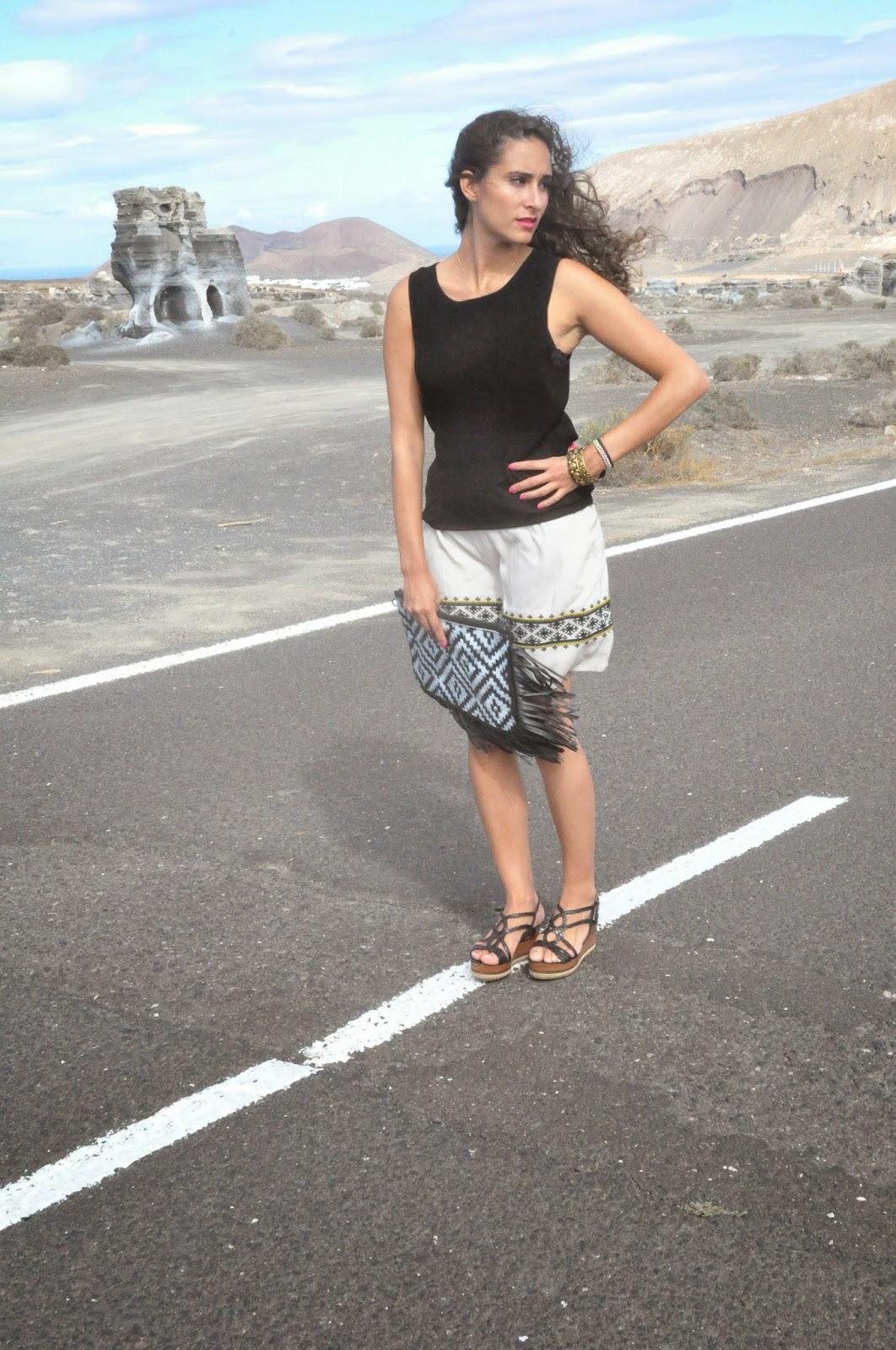 estoy situada en medio de la carretera al lado de la rofera en Teseguite (Lanzarote), con una falda color crema, camiseta negra y cuñas negras abiertas