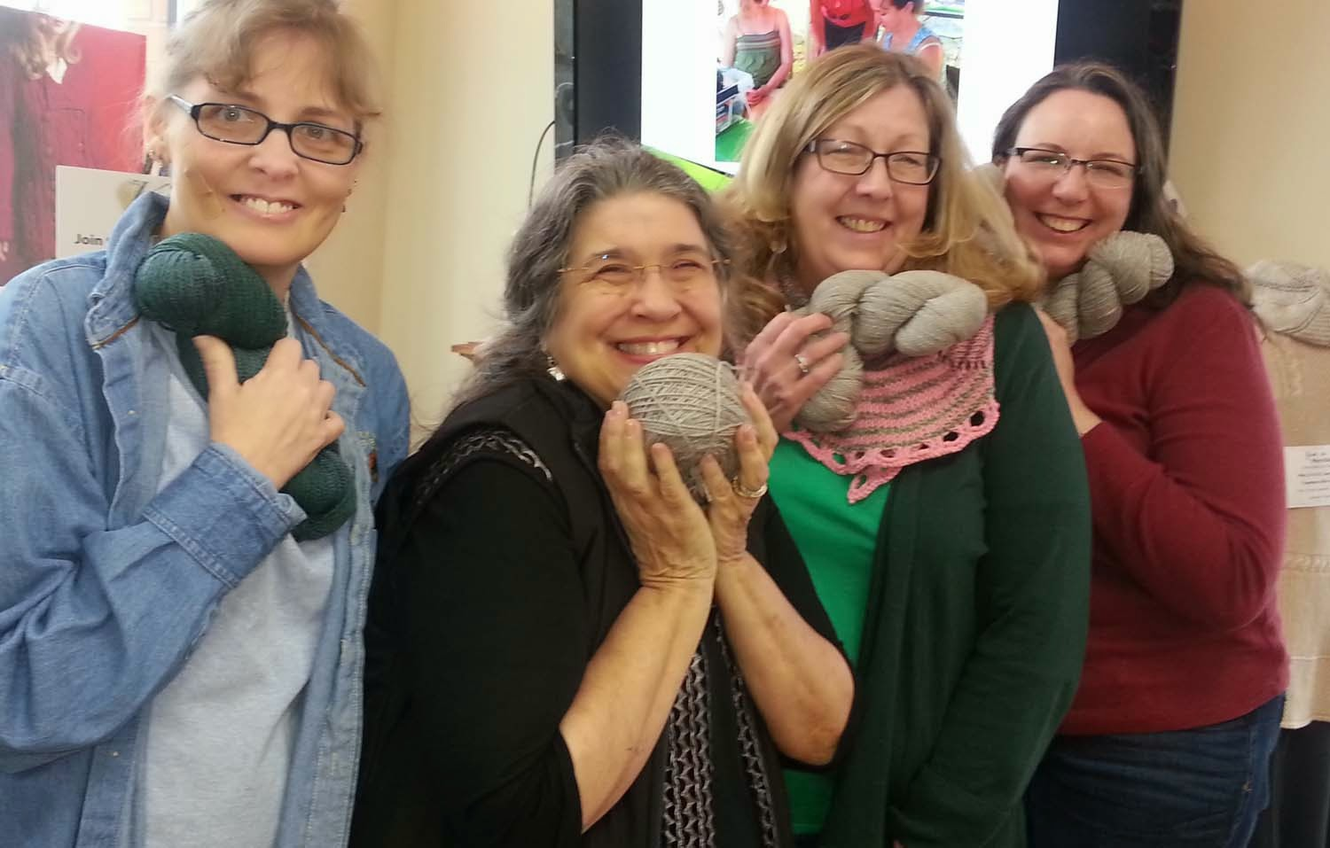 Four knitters hold skeins of luxury yarn available at The Knitting Boutique