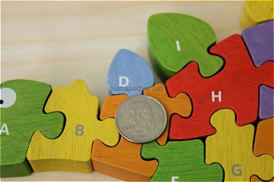 wooden puzzle piece contrast against quarter for size