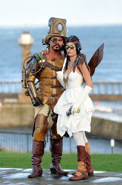 steampunk man and woman with top hat boots dress wings goggles