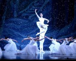 dancing ballaninas in white costumes around a ballarina held in the air by a man in the nutcracker ballet