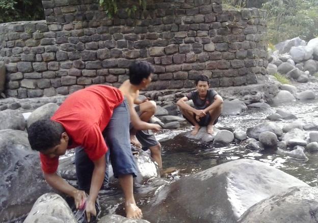 Foto mencuci pakaian di bawah jembatan Wae Mau