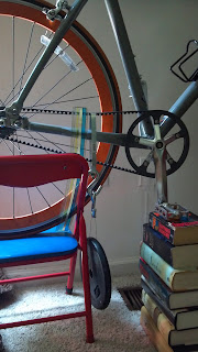 bicycle on a chair and books with a belt drive tension tester set up