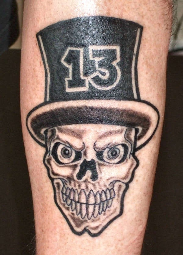 Skull in a hat with number thirteen tattoo