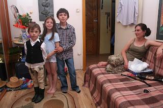 """Szöveg: """"inkább a gyermekeim örömének örülünk tiszta szívből"""". Kép: A három gyermek szamárlétrában, félig egymás háta mögött állva néznek kérkedve a kamerába, míg anyjuk a kép jobb sarkában a kanapéről nézi őket boldog mosollyal."""